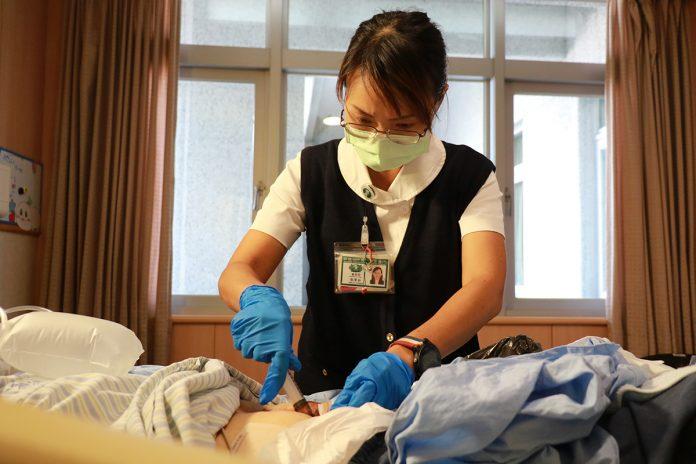 傷造口師張華茹幫住院病人換藥。